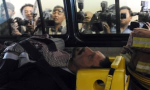 John McAfee is transferred in an ambulance to the national police hospital in Guatemala City on 6 December 2012, after fleeing Belize.
