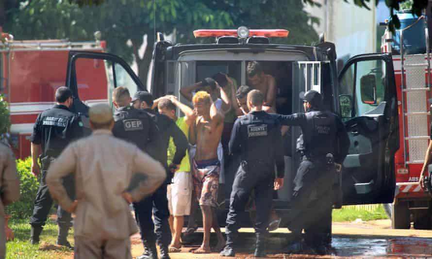Guards bring prisoners back to the facility. Of the 242 who escaped, 99 are still at large, authorities say.