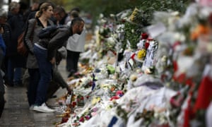 People look at flowers and card tributes placed outside the Bataclan