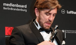 Swedish film director Ruben Östlund poses with the three awards for The Square at the 30th European film Awards in Berlin
