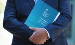 man in a suit holds the Royal Commission Report into Aged Care