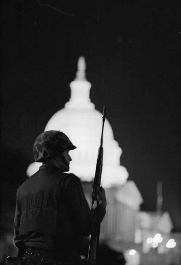 View, from behind, of an armed soldier, in a camouflage helmet, as he enforces a nighttime curfew outside the US Capitol after riots in the wake Dr Martin Luther King Jr's assassination, Washington DC, April 8, 1968.