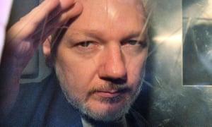 Julian Assange gestures from the window of a prison van