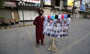 A man sells protective masks after the government ordered the closure of markets in Peshawar, Pakistan,