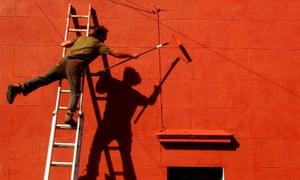 A man on a ladder paintving a house red