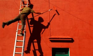 Man on ladder reaching across and balancing on one leg while painting wall