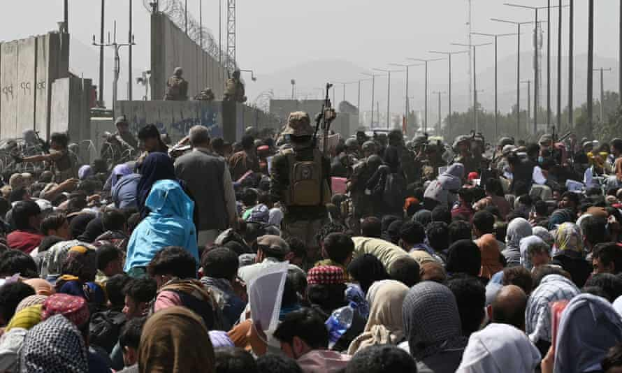 Afghans gather near Kabul airport trying to flee their country after the Taliban took power