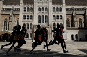 The front runners in the men's marathon cross the courtyard in front of the Guildhall watched by just a few spectators.