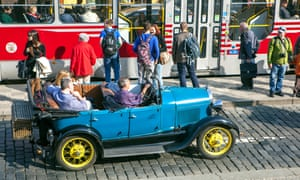 Tourists on a sightseeing tour of Prague in a 'vintage' car