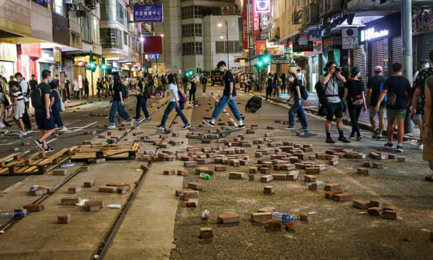 Hongkongers walk past bricks dug up and laid out on the street to slow down incoming police during demonstrations.
