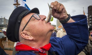 A visitor eats a fish during Vlaggetjesdag, the day on which traditionally the new herring is shipped into the harbour of Scheveningen, the Netherlands