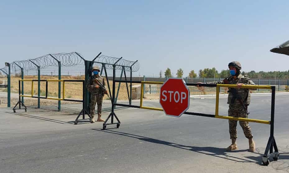 Two soldiers guard a large gate with a stop sign, with barbed wire fencing on each side