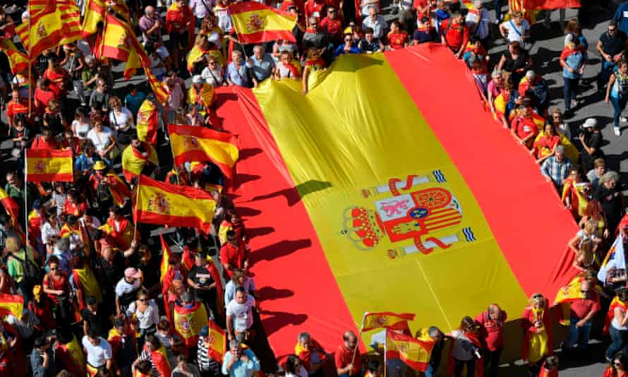 Protesters hold a giant Spanish flag during a demonstration to support the unity of Spain on 8 October in Barcelona.