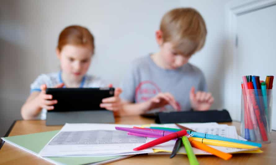 Schoolchildren use iPads to complete online schoolwork at home whilst schools are closed due to the pandemic.