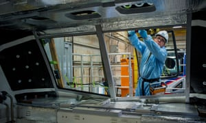 An employee installing the windshield of an Amtrak locomotive at the Siemens Industry Inc. manufacturing facility in Sacramento, California
