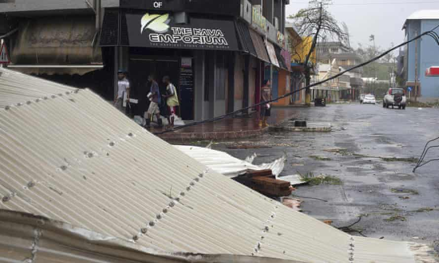 In this image provided by Unicef Pacific, people walk past debris is scattered on a street in Port Vila.