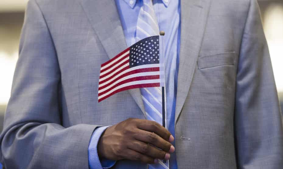 A man holds an US flag prior to taking the citizenship oath.