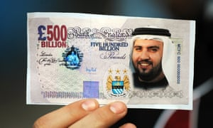 A Manchester City fan holds a mocked-up banknote with Sheikh Mansour's face on it after the club's 2008 takeover.