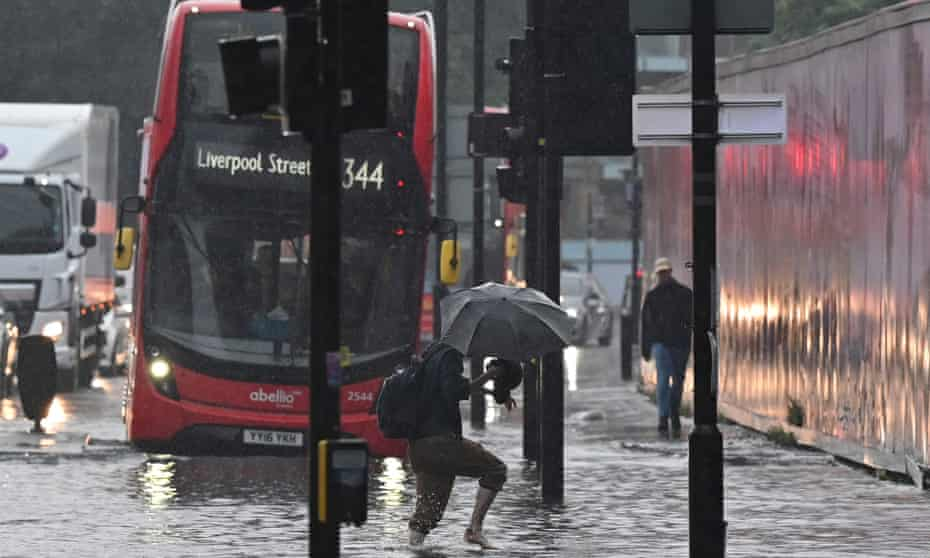 A pedestrian crosses through deep water on a flooded road in east London on 25 July