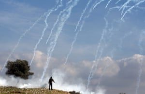 A Palestinian youth looks on as Israeli soldiers fire tear gas during a protest against Israel's separation barrier in the West Bank village of Nabi Saleh.
