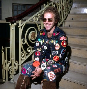 Elton photographed by George Wilkes in 1972, wearing double denim covered in embroidered patches.