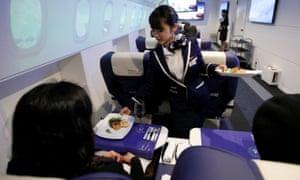"""El personal, vestido de azafata, sirve aperitivos a los huéspedes de la """"First Airlines"""", una instalación virtual de primera clase de experiencia en aerolíneas en Tokio."""