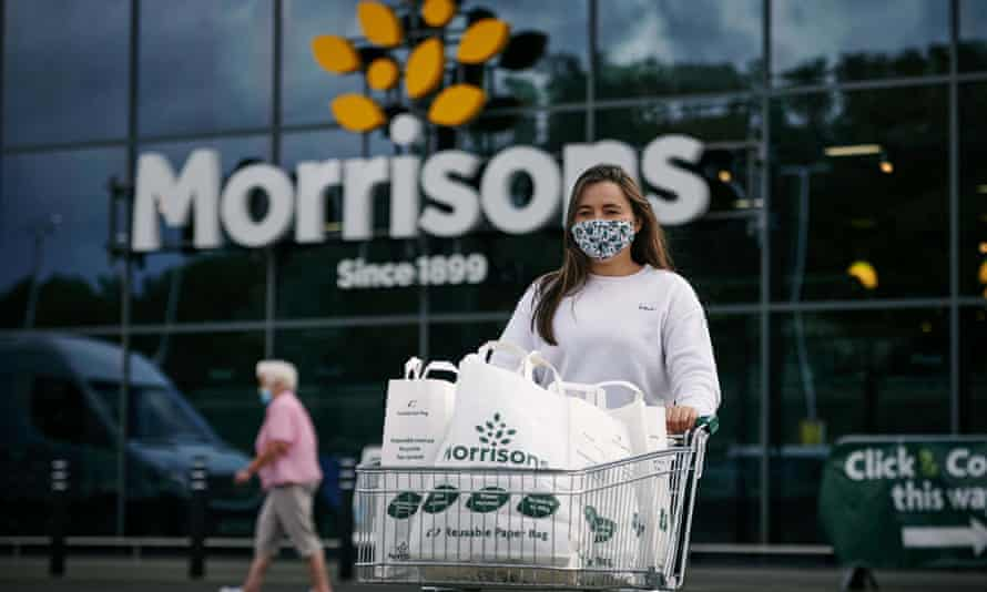 Woman wearing mask leave branch of Morrisons pushing shopped trolley with Morrisons bags