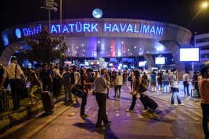 People stand outside the entrance after the attack at Istanbul Ataturk.
