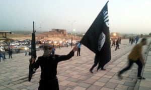 A fighter of Islamic State (also known as Da'esh) holds the group's flag in Mosul, Iraq, in June 2014