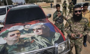 Syrian and Russian soldiers stand beside a car covered by a collage showing presidents Putin and Assad.