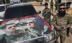 Syrian and Russian soldiers next to a car with images of Assad, his brother Maher and Putin.