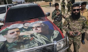 Syrian and Russian solders stand near a car with images of Vladimir Putin and Bashar al-Assad, near Hama.