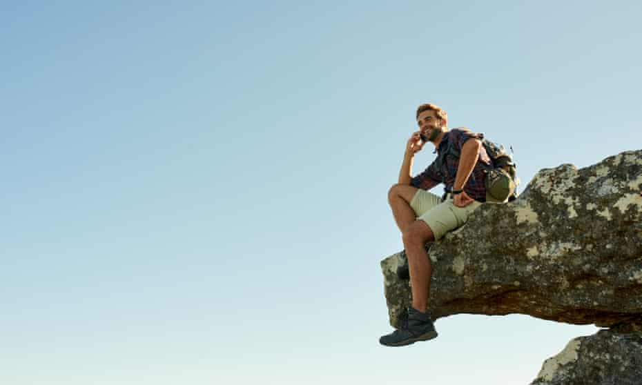 Shot of a hiker talking on his phone while sitting on the edge of a cliff