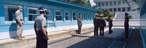 Panmunjom, Demilitarized Zone, Korea, September 2009South and North Korean military police officers standing next to the barrack where the armistice was signed in 1953. The curb marks the demarcation line between the two countries. To the left is an American soldier.