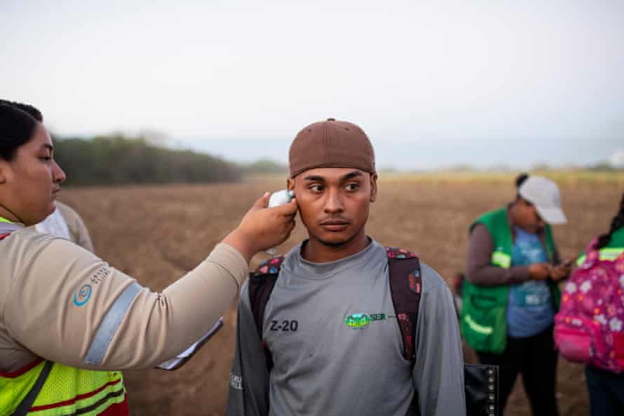 Sugar cane workers get their temperatures taken