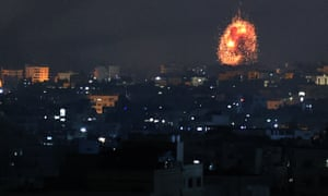 An explosion lights the sky following an Israeli air strike on Beit Lahia in the northern Gaza Strip on Friday.