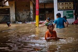 Children wade in their flooded neighbourhood in Jakarta, Indonesia.