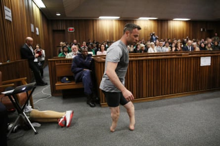 Oscar Pistorius walks across the courtroom without his prosthetic legs