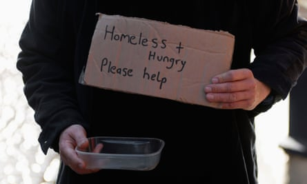 A beggar holds a notice saying: 'Homeless + Hungry. Please help.'