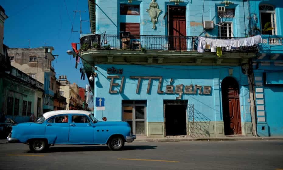 A vintage American car passes a cinema in Old Havana.