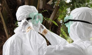Liberian nurses put on protective clothing as preparation to carry the body of an Ebola victim