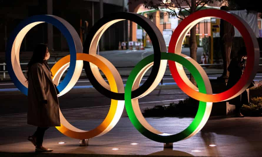 A woman wearing a protective face mask walks past the Olympic rings in front of the Japan Olympics Museum in Tokyo.