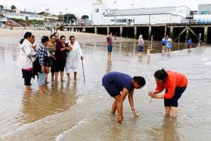 Hindu people wading in the sea