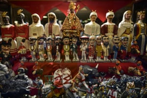 A small figure of Saint Fermín, centre, decorates the window of a shop with other figures of the San Fermín Comparsa – a group of 'giants' who travel through the city during the festiva;