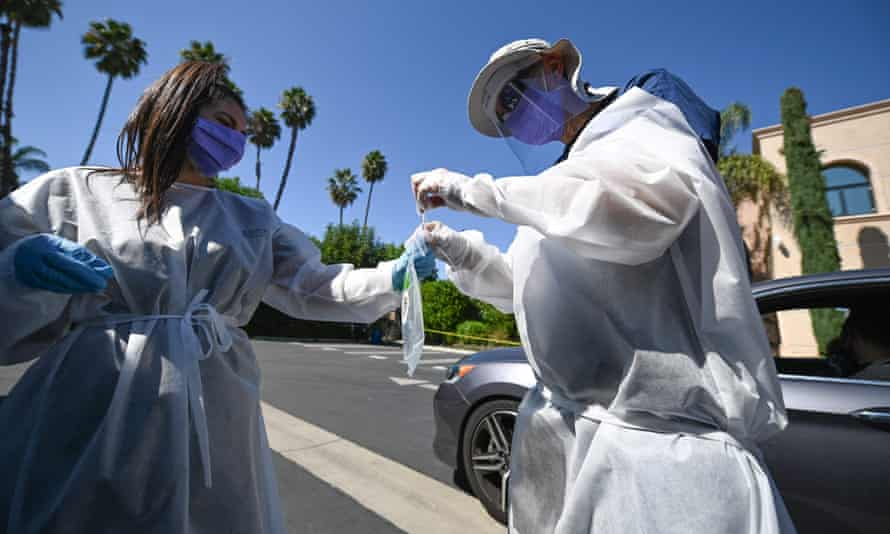 Healthcare workers collect a test sample at a drive-through Covid-19 testing center in Los Angeles.
