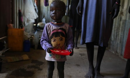 A young girl eats porridge in a sweltering hot shipping container in Bentiu