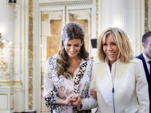 Argentinian President Mauricio Macri's wife Juliana Awada (left) and French President Emmanuel Macron's wife Brigitte laugh during a ceremony at the Casa Rosada