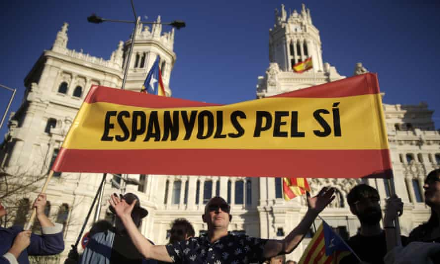 """Supporters of Catalan independence hold a banner reading in Catalan """" Spaniards for Yes"""" during a protest in Madrid."""