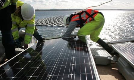 Solar panels being installed on the Queen Elizabeth II reservoir in London. Installations have plummeted since subsidy cuts took effect.
