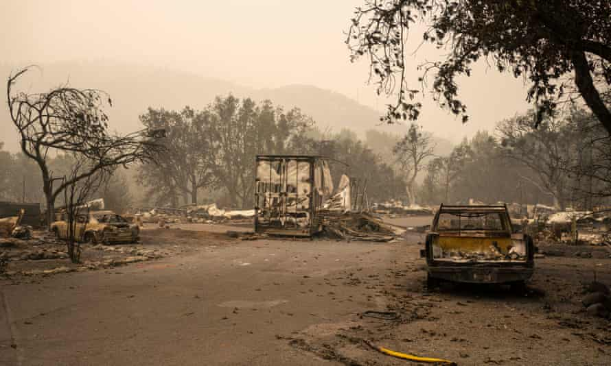 Burned automobiles and a fire hose sit in a mobile home park in Ashland, Oregon. Hundreds of homes in Ashland and nearby towns have been lost because of the wildfires.